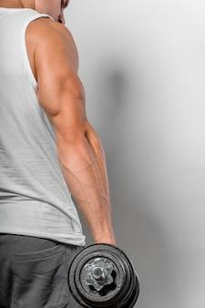 Vista posteriore dell'uomo in forma che tiene il peso