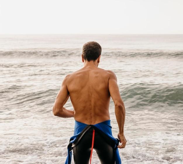 Вид сзади подходит пловец на пляже