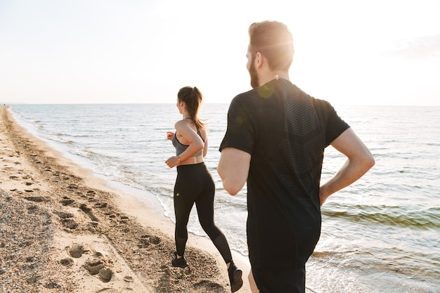 Back view of a fit young couple jogging together