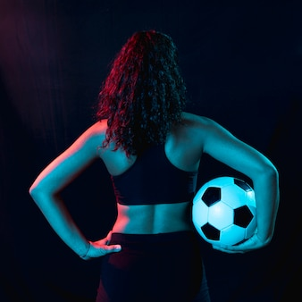Back view fit young girl with soccer ball