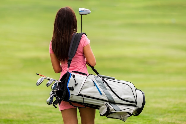 Back view fit young woman with golf clubs