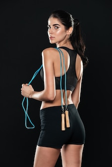 Back view of fitness woman in gym standing over black wall and make sport exercises holding jumping rope