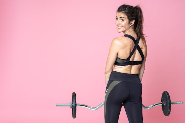 Back view of fitness woman training and smiling