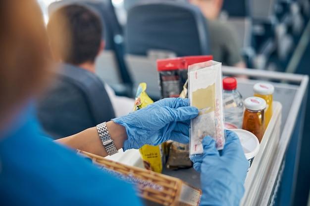 여성 스튜어디스가 일등석 승객에게 식사를 제공하는 동안 스낵과 음료가있는 테이블의 초점을 맞춘 뒷면 이미지
