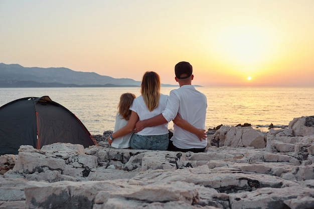 Back view of friendly family admiring setting sun over sea.