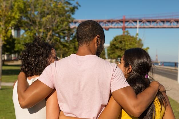 Punto di vista posteriore degli amici che abbracciano nel parco