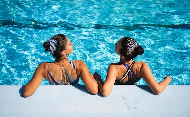 Вид сзади друзей, расслабляющихся в бассейне