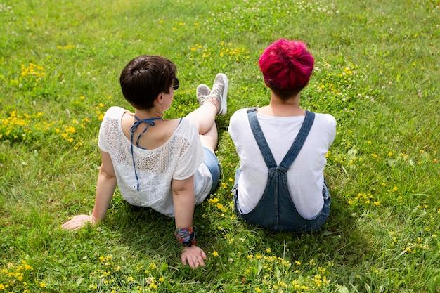 Amici di vista posteriore che si siedono sull'erba