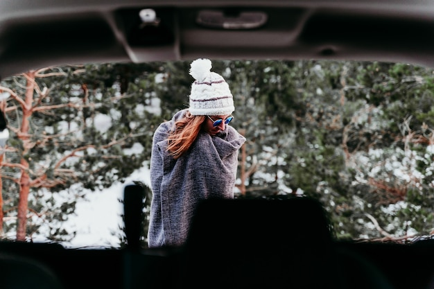 Back view from inside a car of young woman outdoors wearing stylish hat. snowy mountain