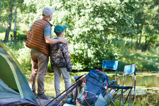 Back view full length portrait of father and son looking at lake while enjoying camping trip together, copy space