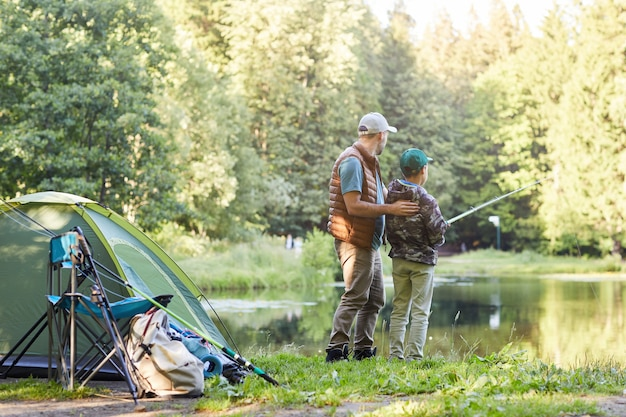 Back view full length portrait of loving father teaching son fishing while enjoying camping trip together, copy space