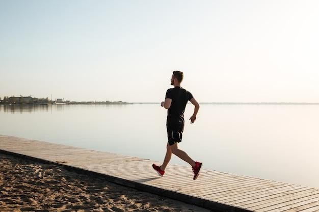 実行している健康的なスポーツマンの背面図の完全な長さの肖像画