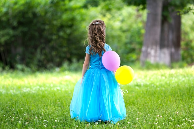 Back view full-length portrait of pretty little blond long-haired girl in long blue dress with colorful balloons standing in blooming field on blurred green trees