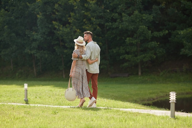 Back view full length portrait of romantic adult couple embracing while walking on path across green lawn in nature scenery