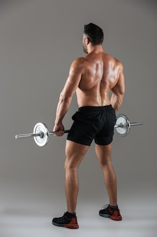 Back view full length of a strong shirtless male bodybuilder