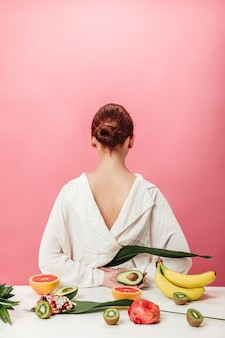 Back view of ginger woman with exotic fruits. studio shot of girl in white shirt with bananas, grapefruits, garnet. kiwi and avocado on pink background.