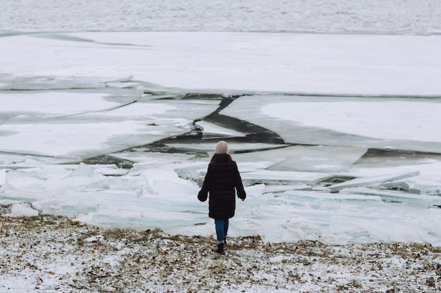 Back view of girl on the background of winter river with cracked ice. landscape with frozen river.