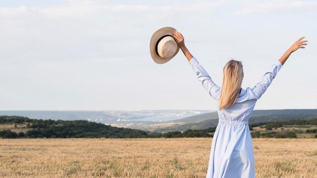 Вид сзади девушка, наслаждающаяся природой с копией пространства
