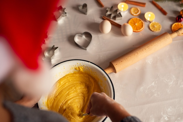 Back view of a girl in red santa hat making dough in the bowl