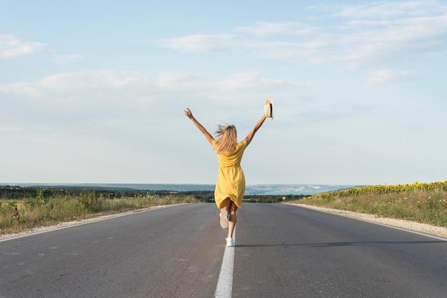 Вид сзади девушка, бегущая посреди улицы