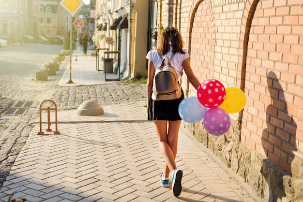 Back view girl teenager school student with balloons