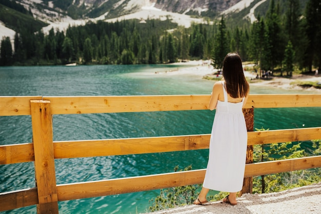 Back view of girl in a white dress stand near lake with emerald water.