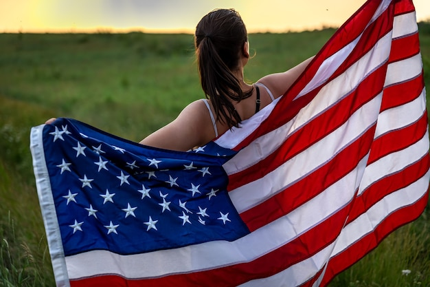 Back view of a girl with an american flag running on the grass in the field