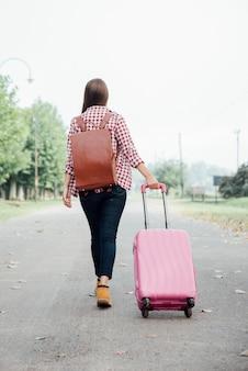 Вид сзади девушка с рюкзаком и розовым багажом