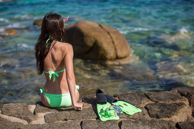 Back view of girl with equipment on large stones ready for snorkeling