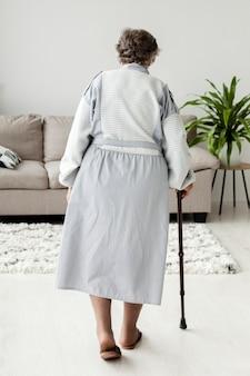 Вид сзади бабушка гуляет дома