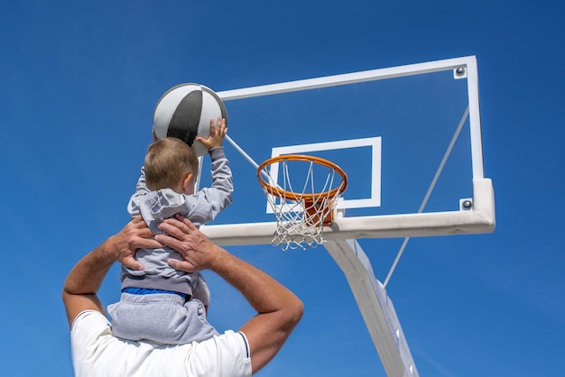 Back view of a grandson sitting on his grandfather's shoulder throwing a basketball into a hoop