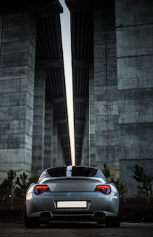 Back view of a grey car standing under the bridge.