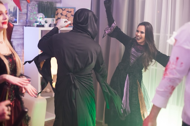 Back view of grim reaper having fun at halloween celebration with group of friends.