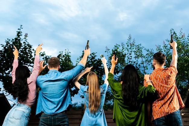 Vista posteriore gruppo di amici, alzando le mani