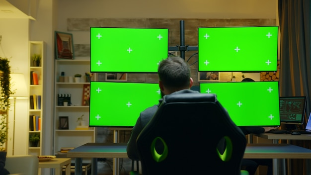 Back view of hacker using computer with multiple screen with green mockup.