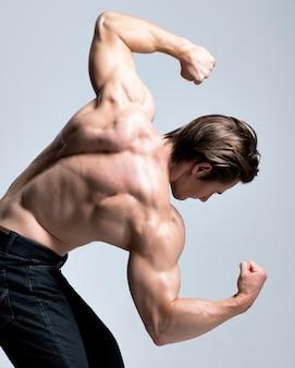 Vista posteriore di un uomo bello con sexy muscoloso bel corpo in posa.