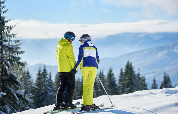 Back view of happy couple skiers standing on mountain edge, holding hands, enjoying winter mountain panoramic landscape