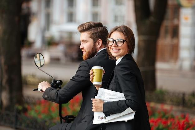 Back view of happy elegant couple rides on modern motorbike