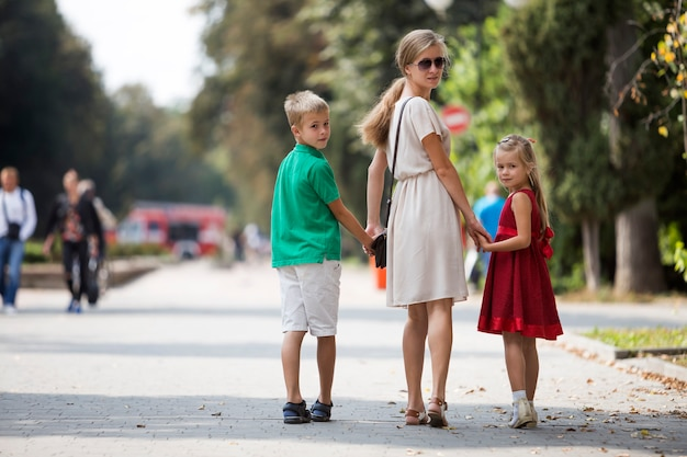 Back view of happy family, young blond long-haired woman looking back holding hands with two cute children, daughter and son on sunny park alley on green trees bokeh  on warm summer day.