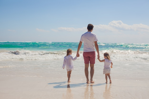 Back view of happy father and his adorable little daughters walking on sunny day