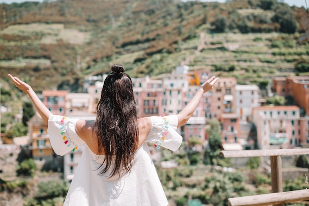 Back view of happy girl background beautiful view of manarola, cinque terre, liguria, italy