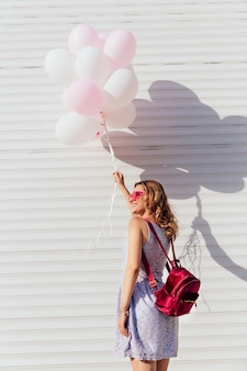 Back view of happy girl in sunglasses, holding air balloons, standing opposite the white wall