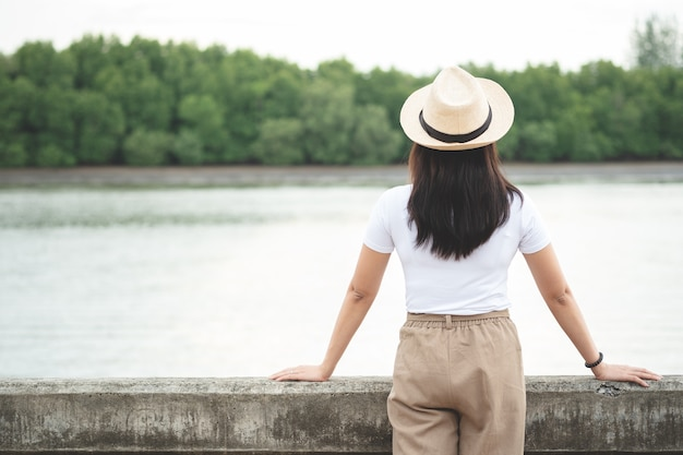 Back view of happy hipster woman in hat standing and looking at river in evening sunset.