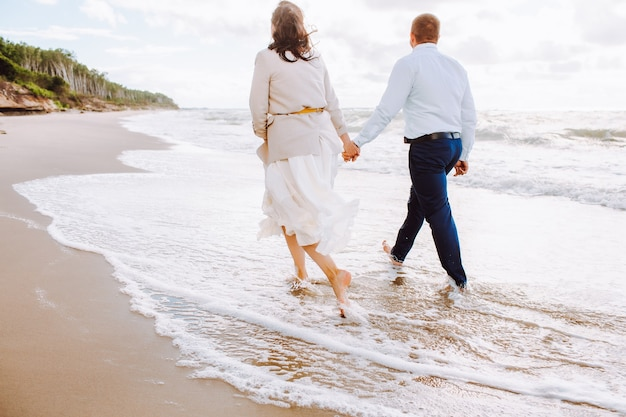 Back view of happy just married middle age couple walk at beach against blue sky with clouds and have fun on summer day.
