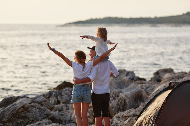 Back view of happy parents with little daughter, sitting on daddy neck and admiring setting sun over sea near tent. family embracing and pointing by hand at sea and looking closely to that side.