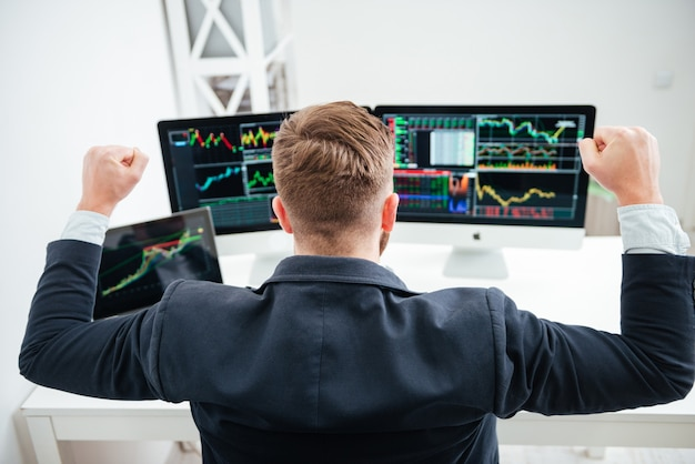 Back view of happy successful businessman sitting with raised hands and working with computer in office