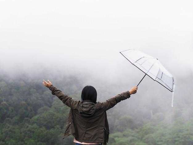 背面の幸せな女性観光客は、緑の熱帯雨林の背景の上に傘を保持します。
