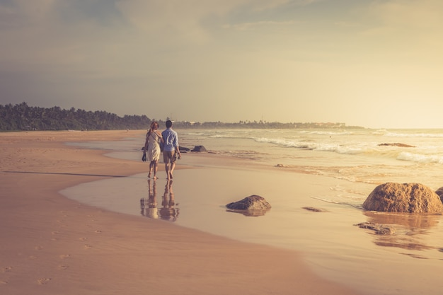 Back view of happy young couple walking on a deserted tropical beach. toning photo