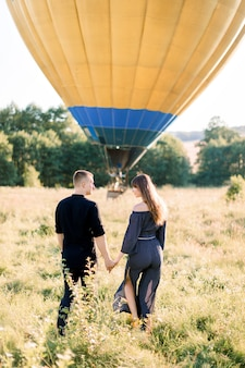 Back view of happy young woman and man in summer field, ready to make balloon tour, standing in front of air balloon holding hands