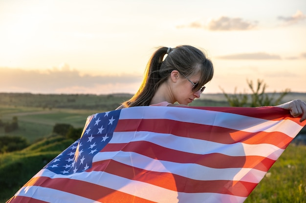 Back view of happy young woman posing with usa national flag outdoors at sunset. positive girl celebrating united states independence day. international day of democracy concept.